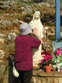 Praying to Our Lady statue at the Blue Cross