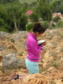 Young woman reading religious book at the Apparition Hill Podbrdo